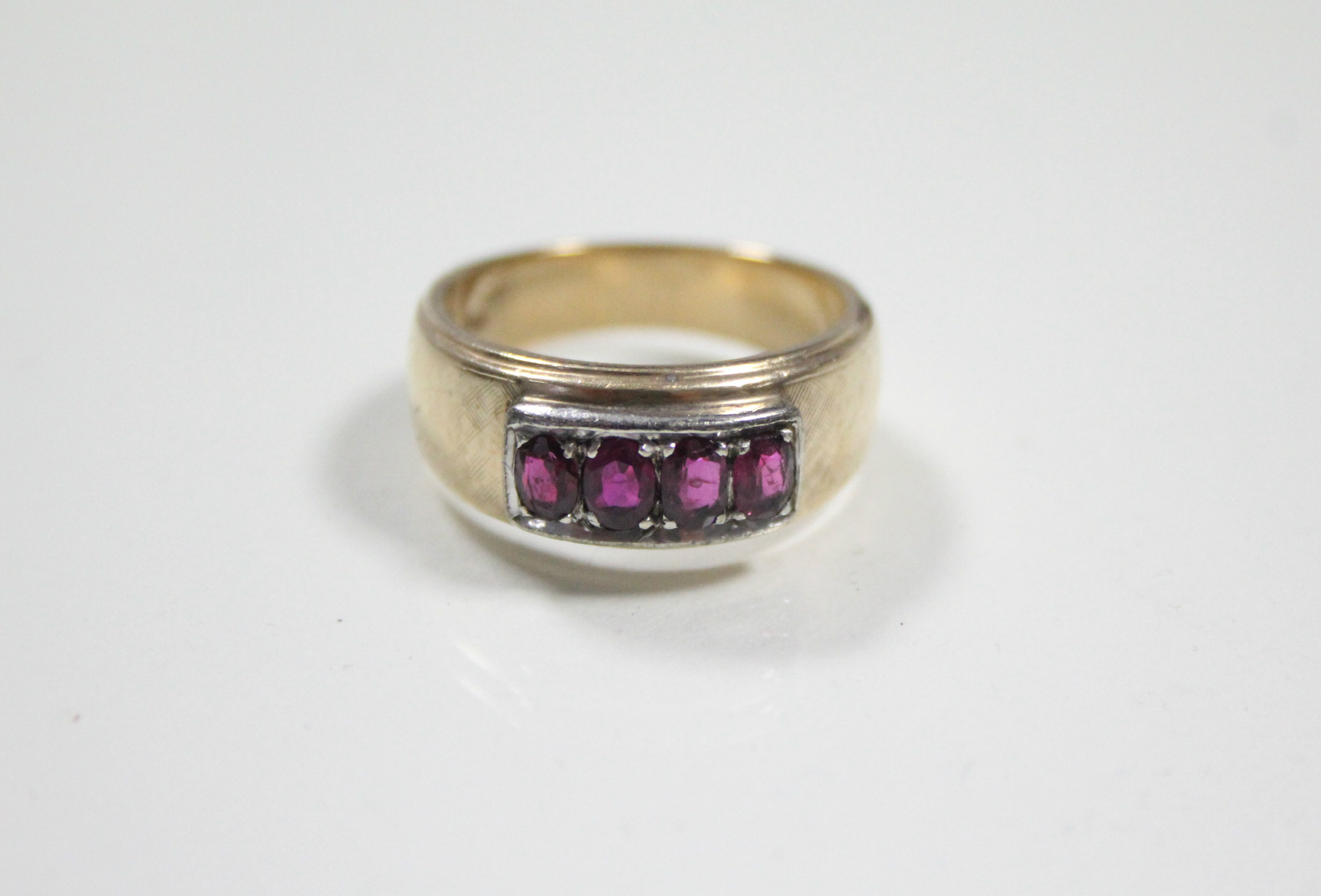 Lot 51 - A 14K gent's ring set four oval rubies.