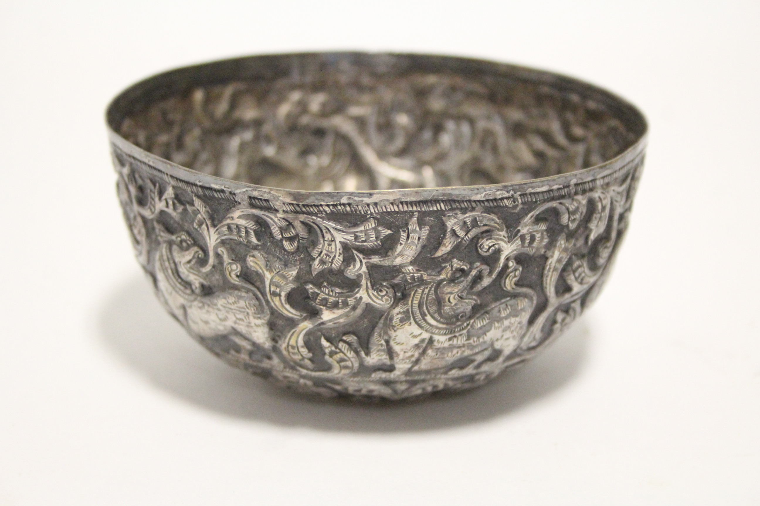 """Lot 46 - An Indian 4¾"""" diam. deep bowl embossed with mythical beasts & leaf-scrolls."""