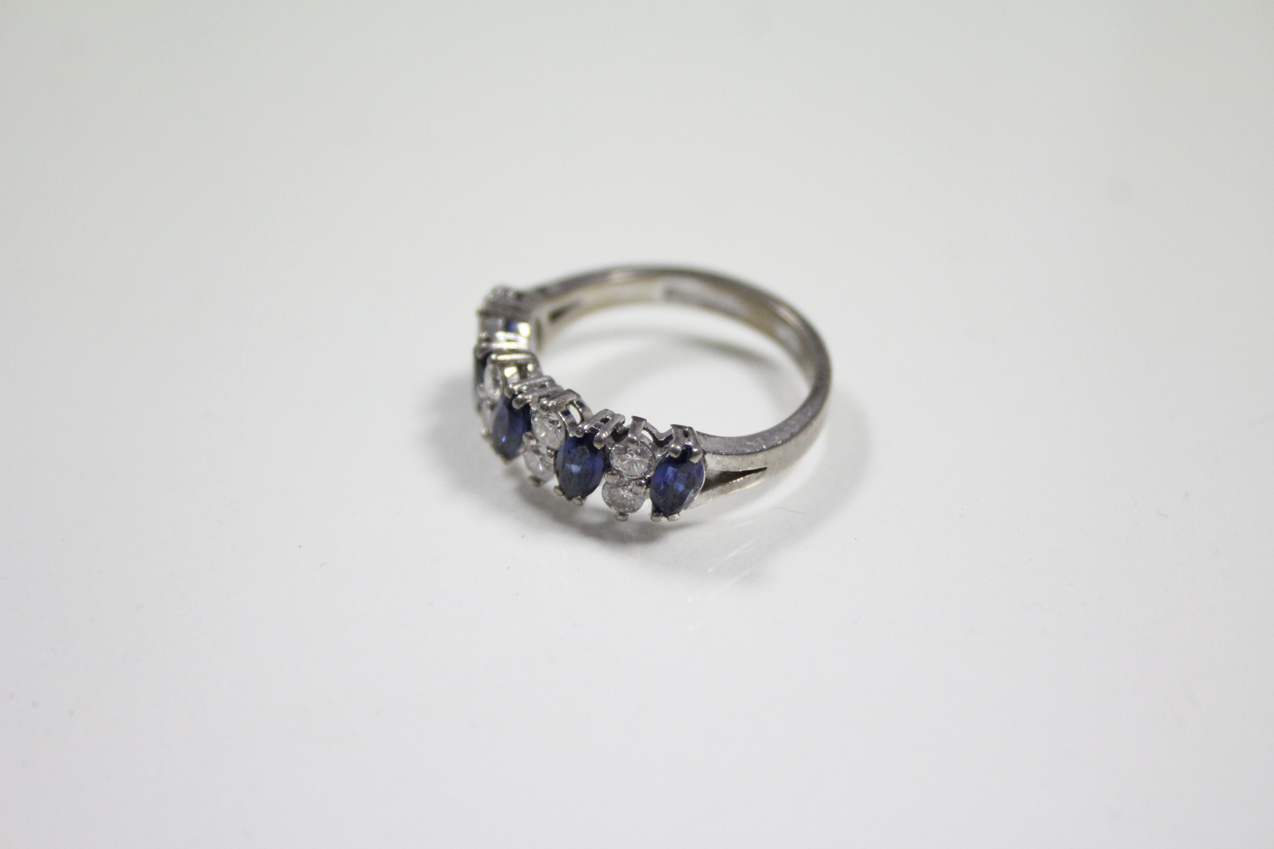 Lot 56 - A SAPPHIRE & DIAMOND RING, the five navette-shaped sapphire set at a slight angle & divided by