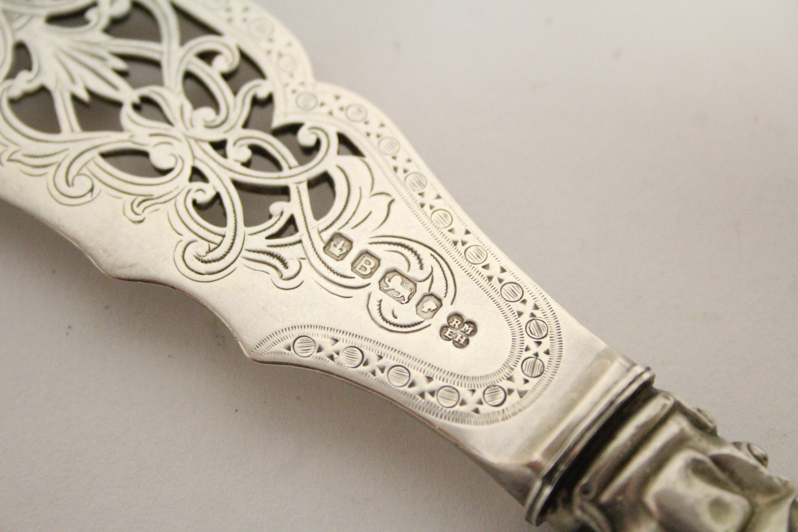 Lot 8 - A pair of Victorian pierced & engraved fish servers with carved ivory handles; Sheffield 1869, by