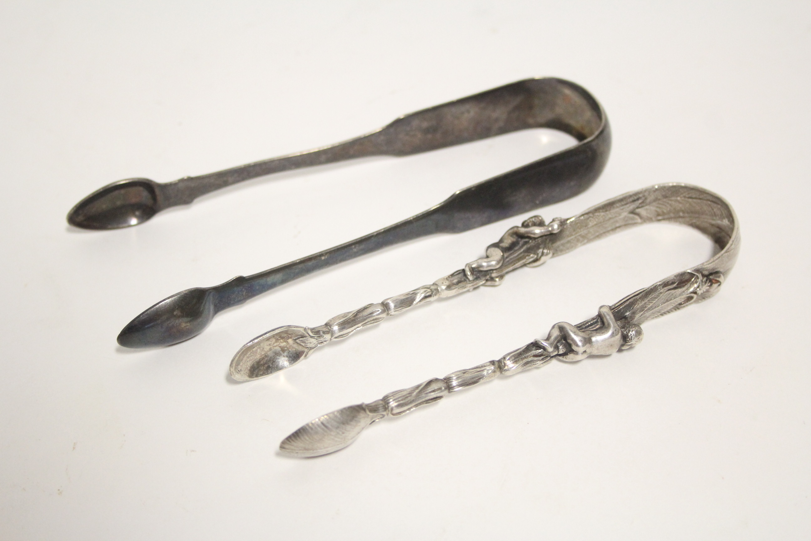 "Lot 12 - A pair of Victorian ""Banana Palm"" sugar tongs, each cast stem with a figure climbing up the trunk,"