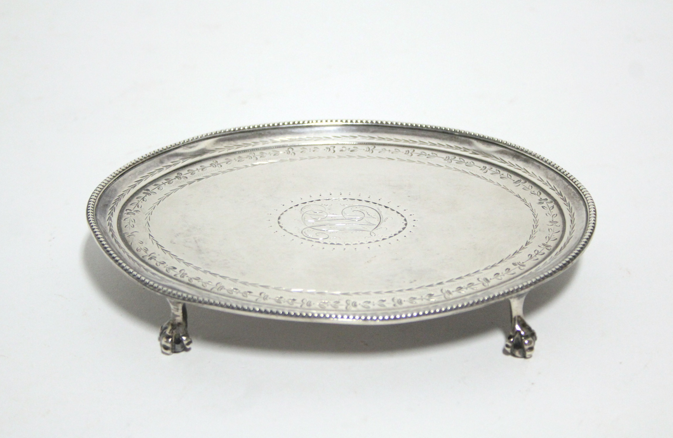 Lot 27 - A George III oval teapot stand with beaded rim & engraved floral narrow border, on four claw-&-