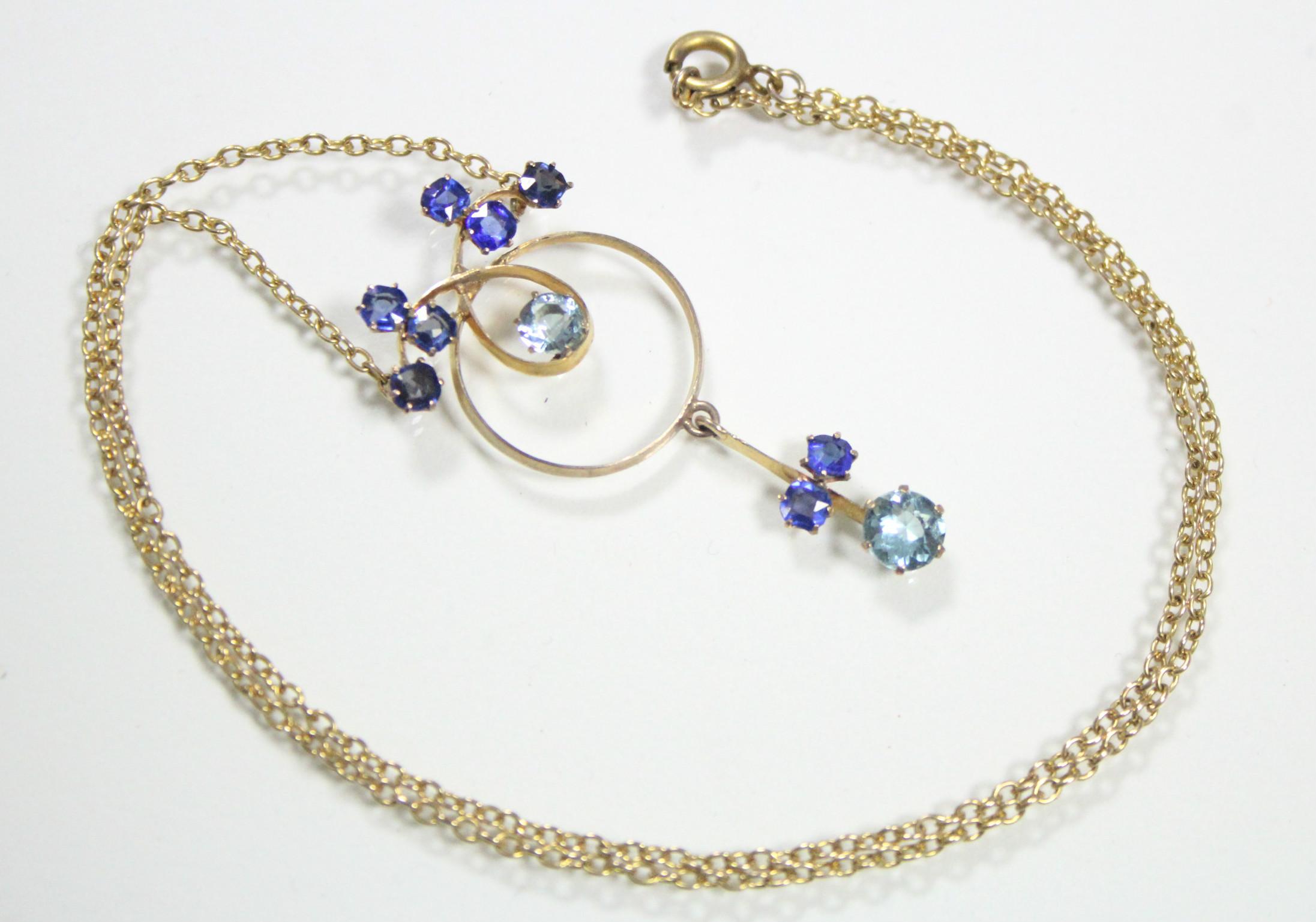 Lot 57 - A 9ct. gold circular openwork pendant set aquamarine & sapphires, pendant drop below, on fine-link