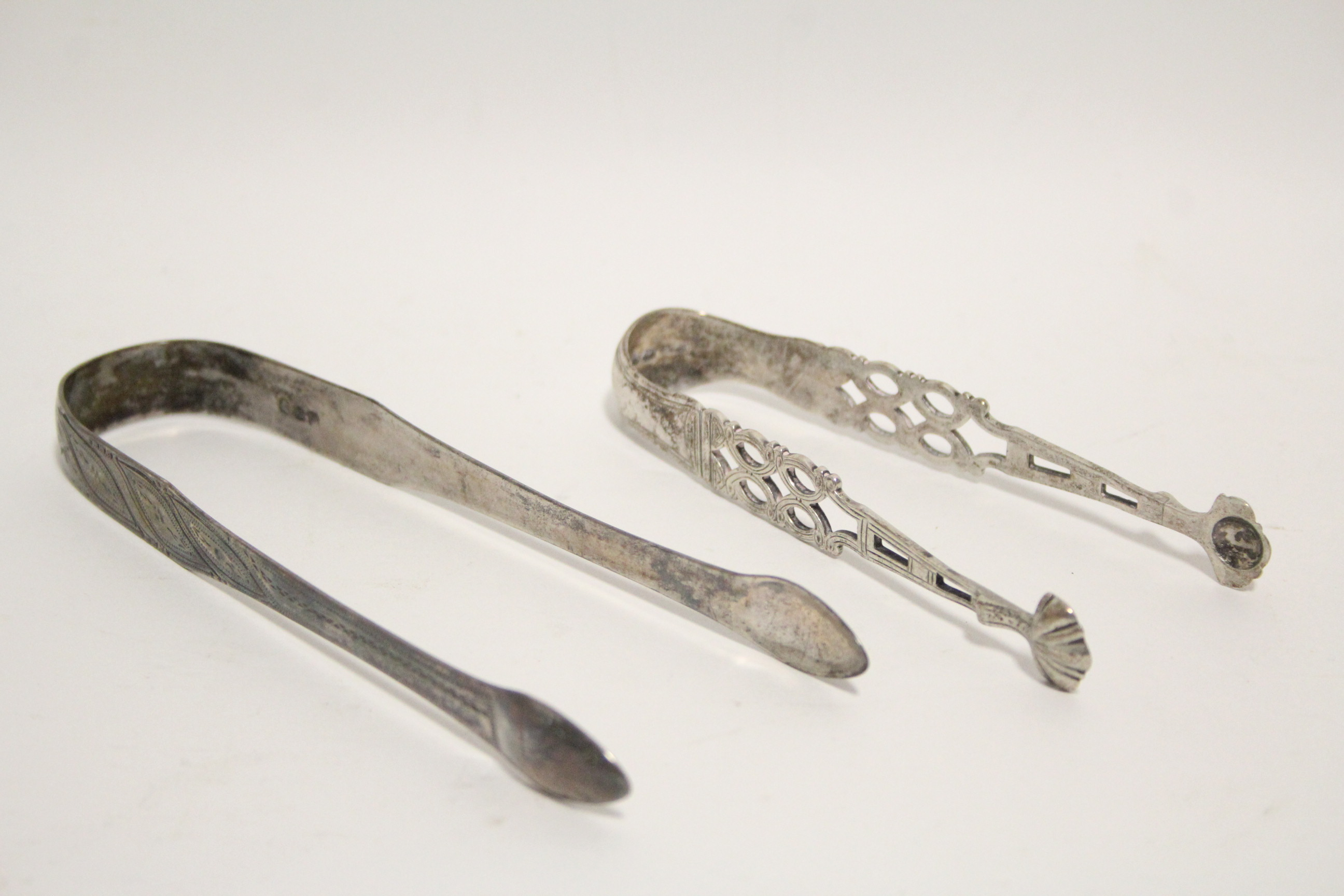 Lot 39 - A pair of Victorian sugar tongs in the mid-18th century style, with pierced stems & shell bowls,