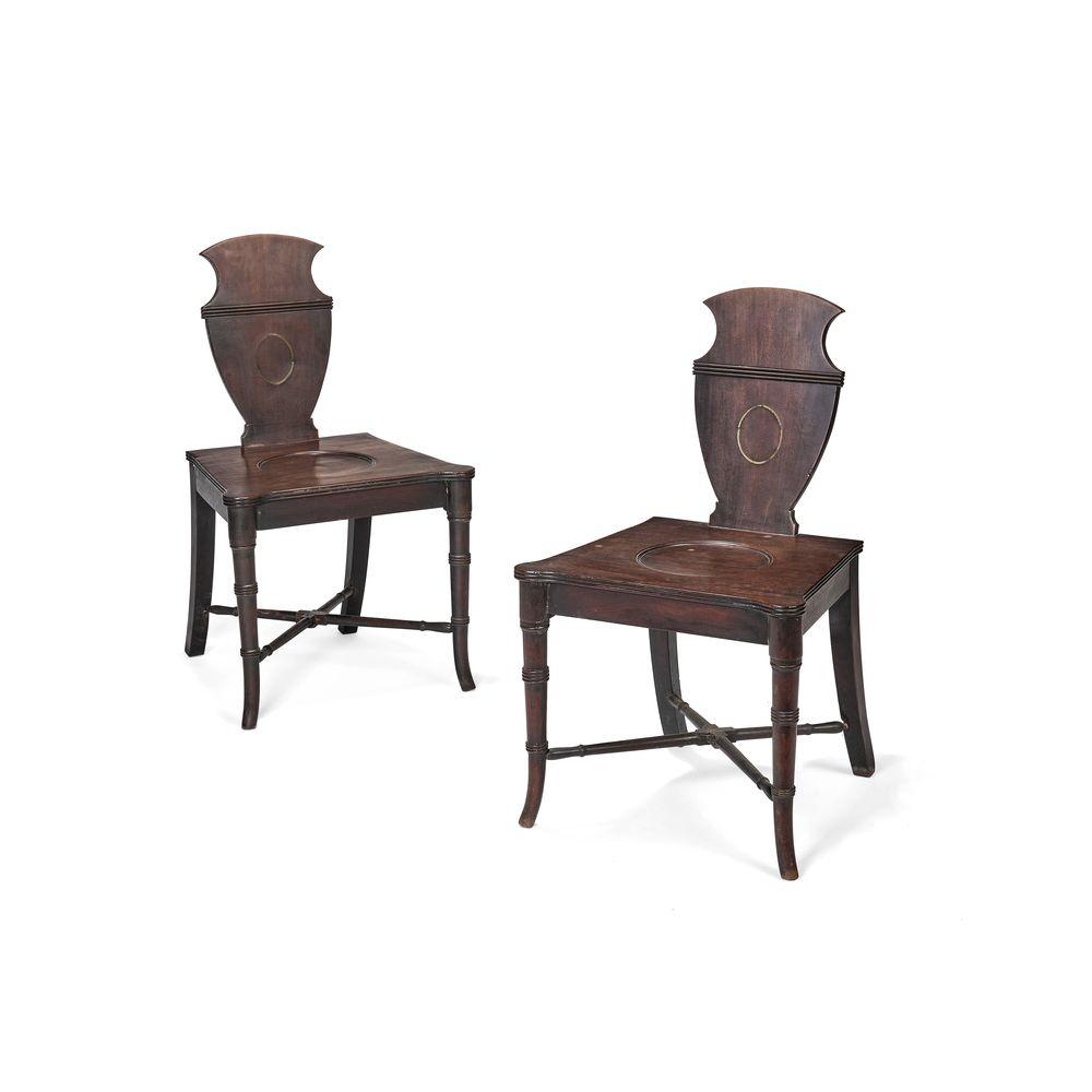 A pair of late George III mahogany hall chairs, circa 1800
