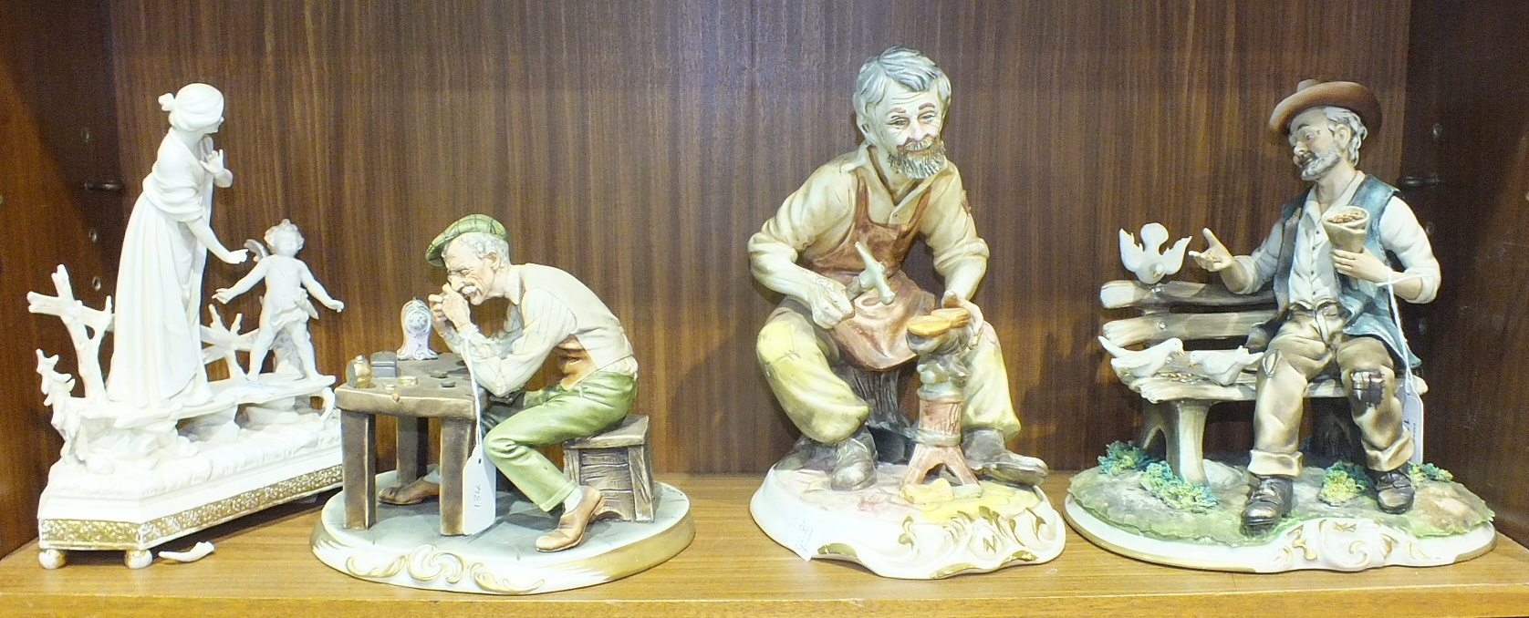 Lot 134 - A Capo-di-monte-style figure depicting a clock maker, 20cm high, two other similar figures and a