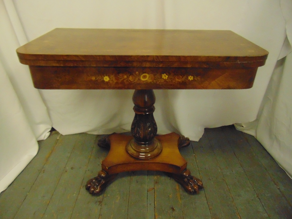 A late Victorian rectangular walnut and mahogany games table on quatrefoil base with claw feet