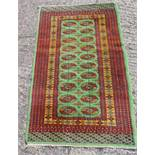 A Persian wool carpet green ground with repeating motif design, predominately red and green border