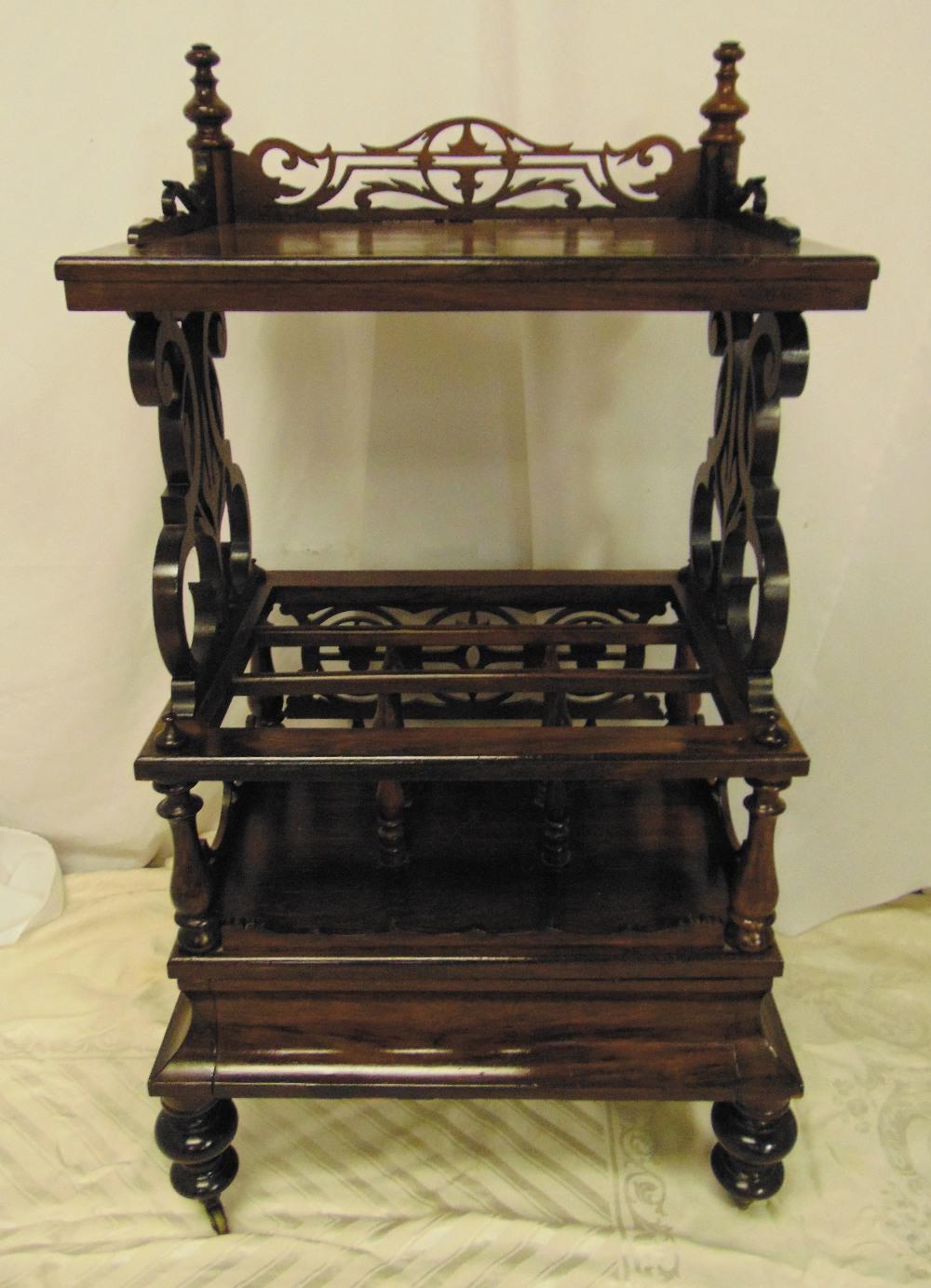 A Victorian mahogany rectangular whatnot cum magazine rack with pierced scroll sides on four bun