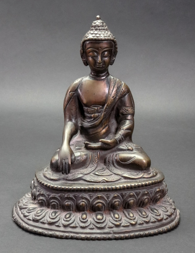 Lot 245 - A gilt metal figure of Buddha, seated cross legged, on a lotus flower, 20cm high. Illustrated.