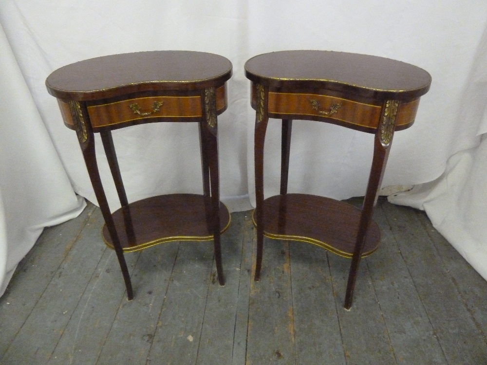 Lot 12 - A pair of Kingswood kidney shaped side tables with gilded metal mounts, on four tapering cabriole