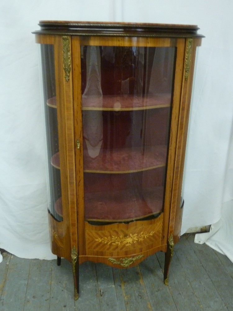 Lot 8 - An oval Kingswood inlaid glazed display cabinet with gilt metal mounts, hinged glazed door on four