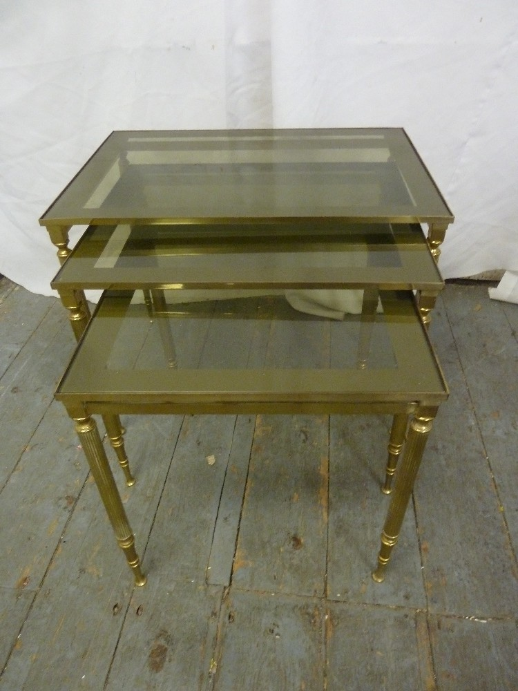 Lot 24 - A gilded metal and glass nest of three rectangular tables on four tapering cylindrical legs