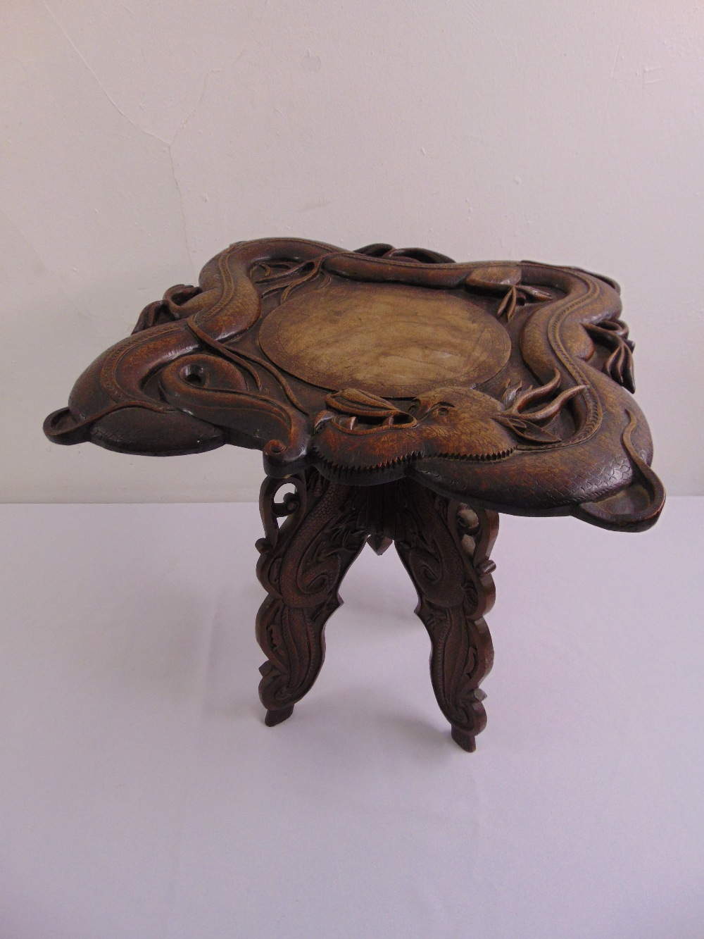 Lot 29 - A Chinese hardwood side table shaped square carved with a dragon in deep relief on four scrolling