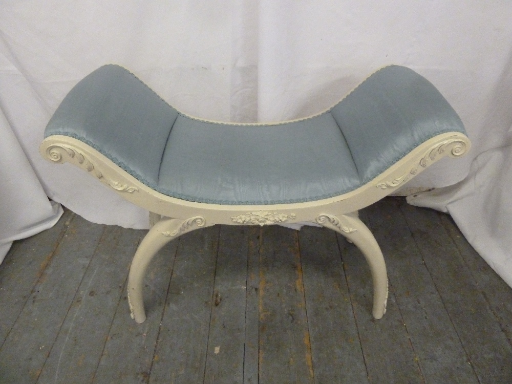 Lot 43 - A curved white painted upholstered boudoir stool on sabre legs