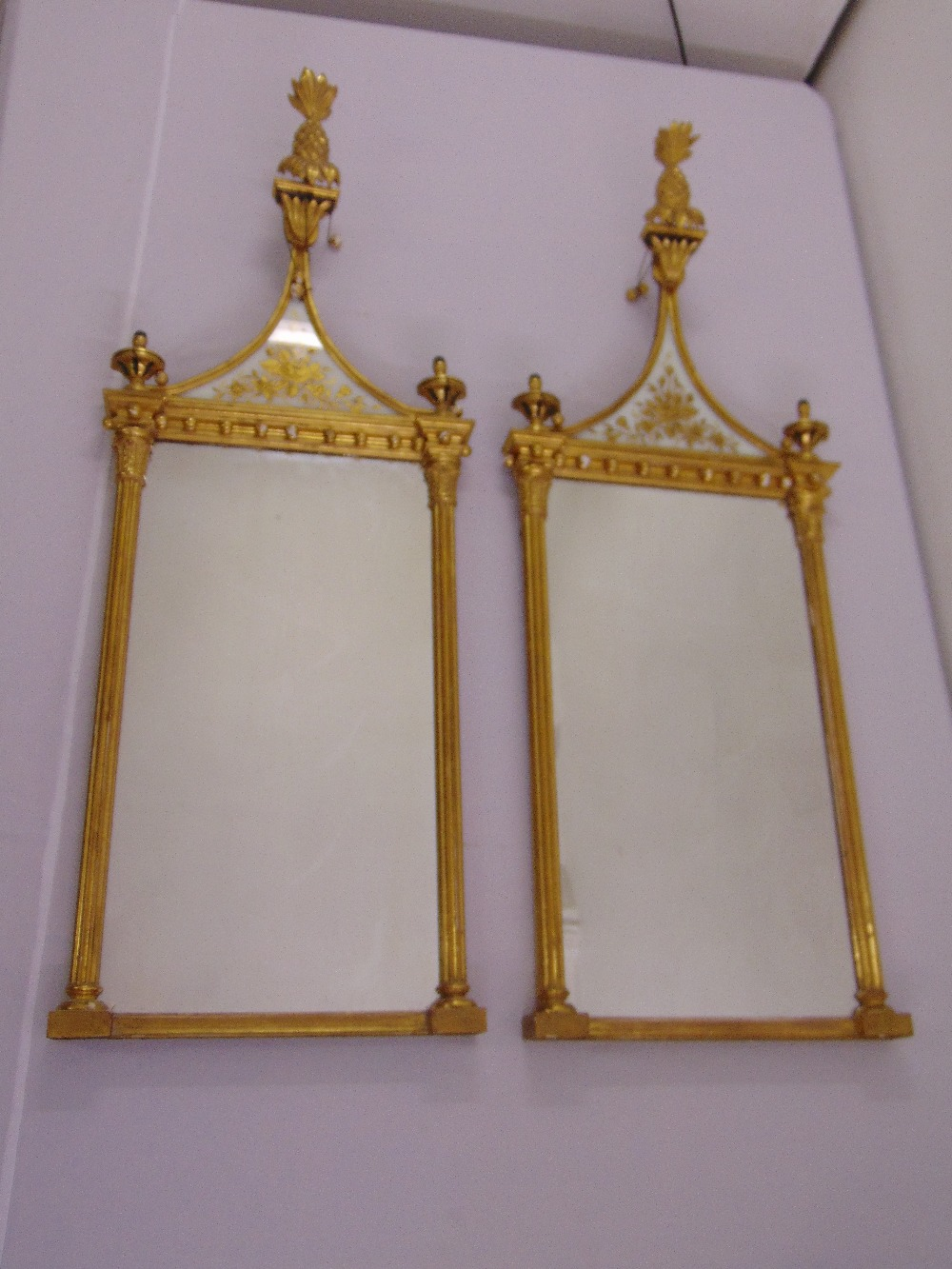 Lot 50 - A pair of neo-classical rectangular wall mirrors surmounted by pineapple finials