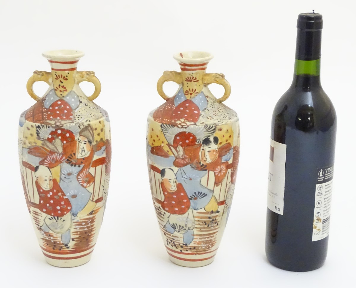 Lot 34 - A pair of Imari style vases with decorative twin handles,