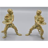 Lot 32 - A pair of brass Venetian style candlesticks cast as robed monkey attendants,