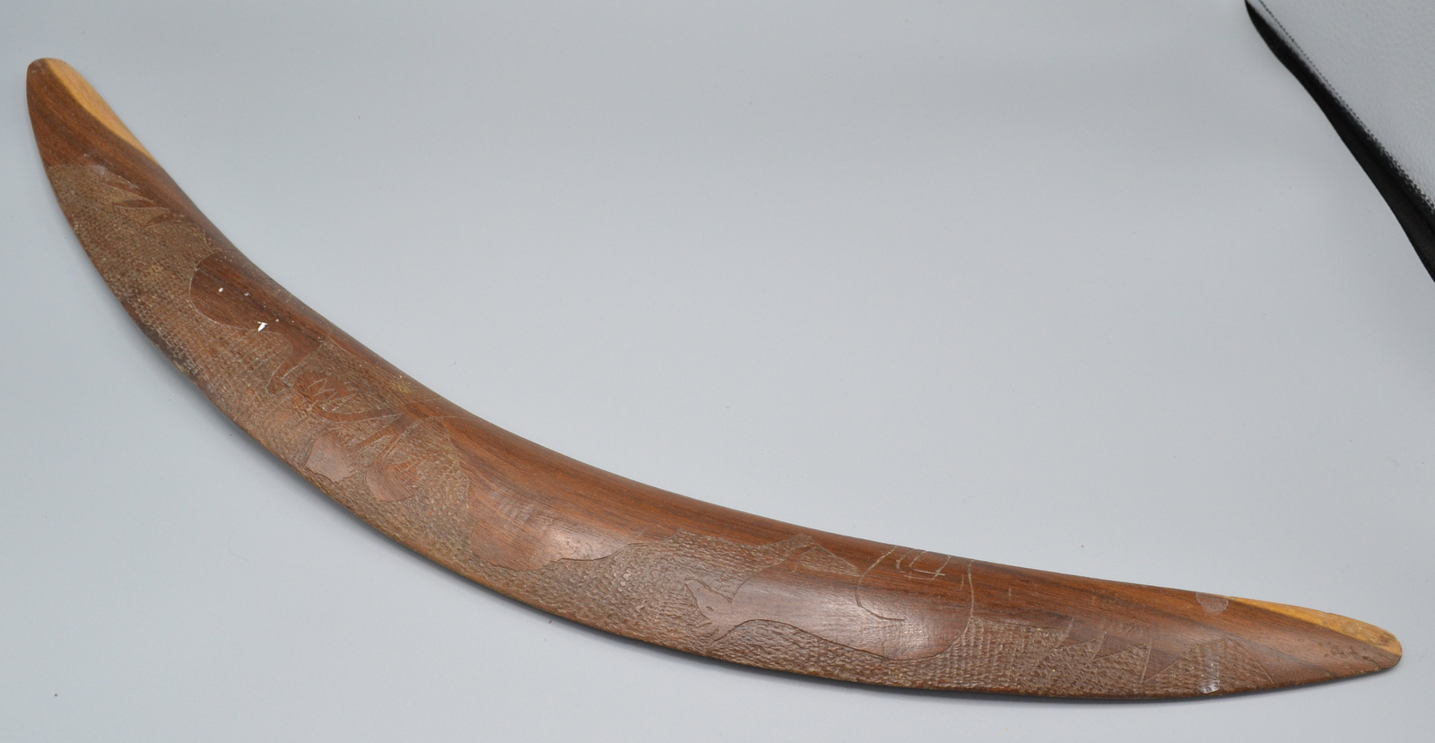 Lot 59 - A boomerang carved with a kangaroo and emu in a landscape, length 63cm.
