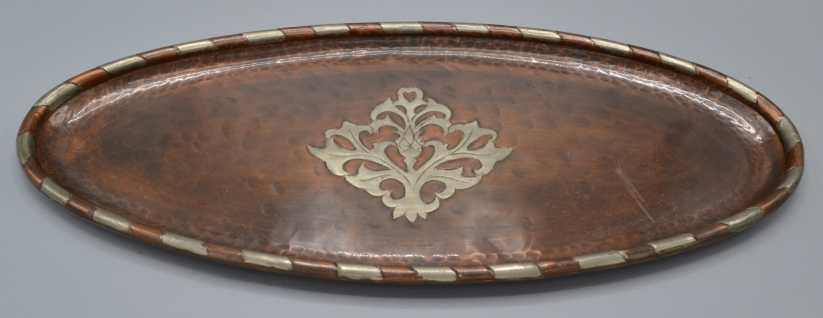 Lot 27 - Hugh Wallis, an Arts and Crafts narrow, oval, planished copper tray,