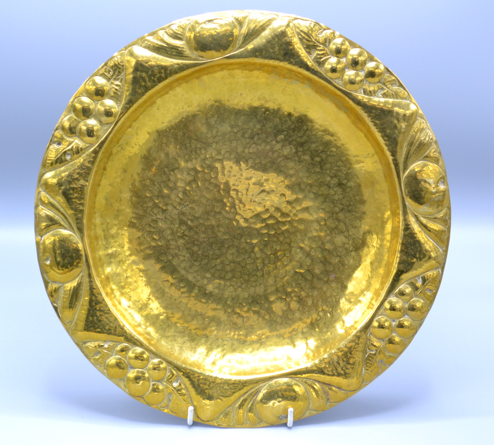 Lot 3 - A brass Arts and Crafts dish with a fruit decorated repousse rim and planished centre, impressed F.