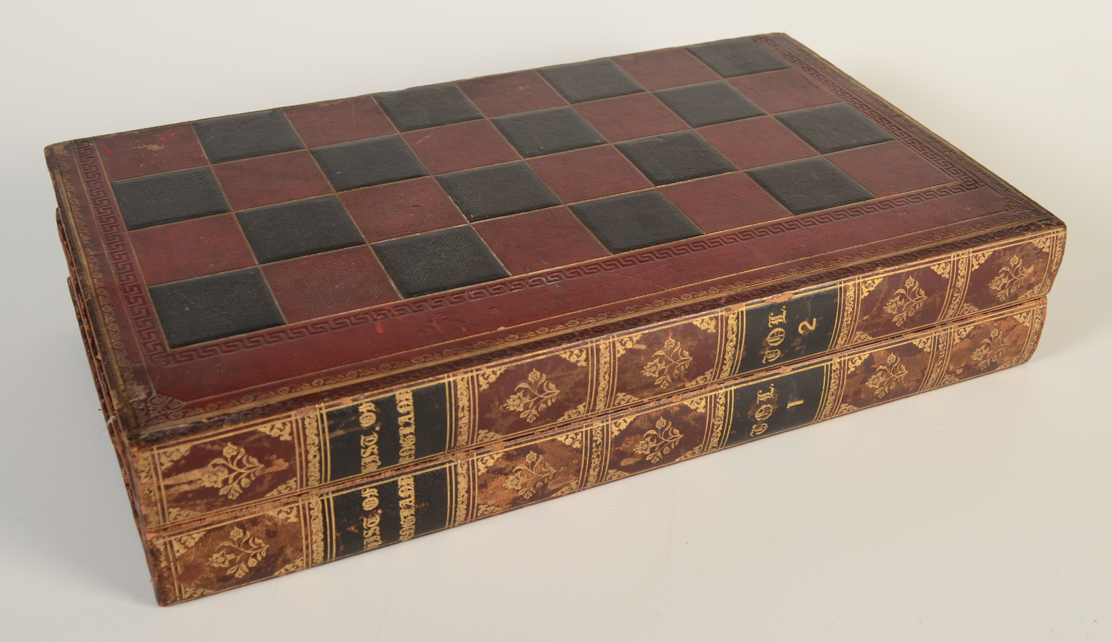 Lot 13 - A set of red and natural bone draughts, in a good tooled gilt leather bound book case/board.
