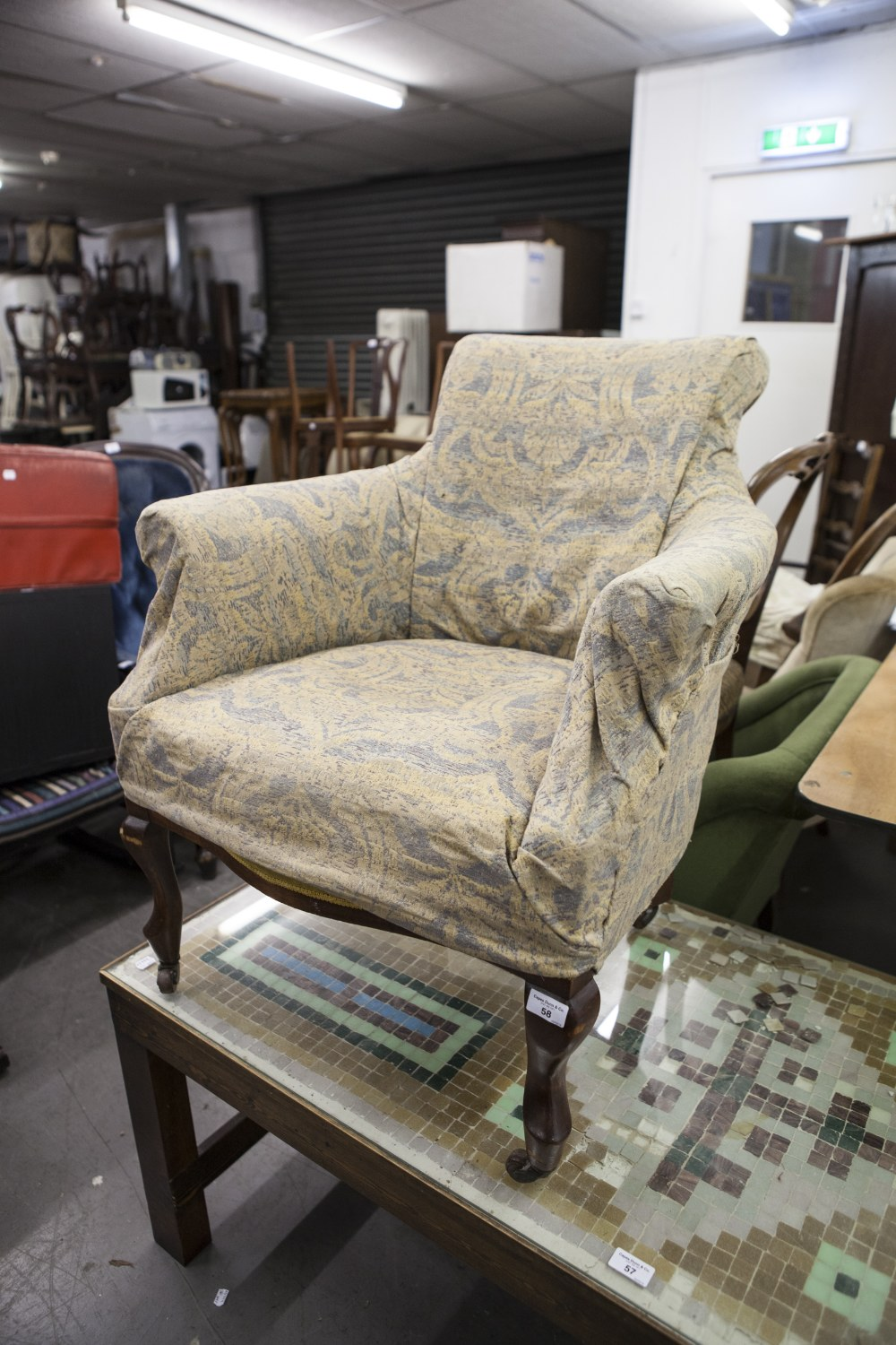 Lot 58 - A SMALL EARLY TWENTIETH CENTURY TUB SHAPED EASY CHAIR WITH SCROLL FRONT SUPPORTS