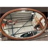 An oak framed oval wall mirror