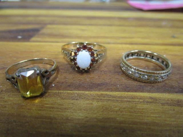 Lot 44 - A 9ct gold opal and garnet ring, a yellow metal and white stone full eternity ring and a 9ct gold