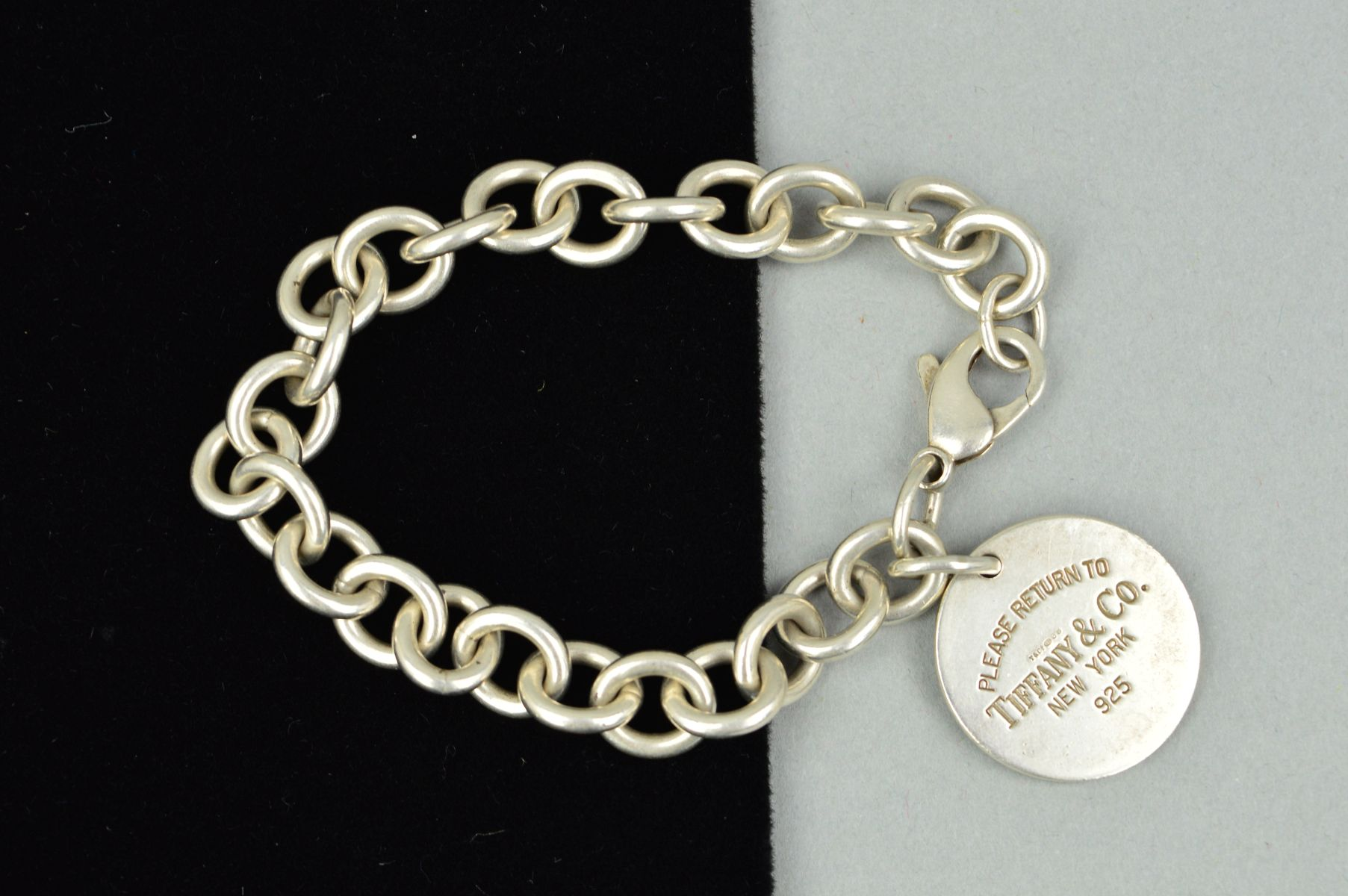 Lot 26 - A TIFFANY & CO. SILVER BRACELET, the belcher link bracelet suspending a circular panel stamped '