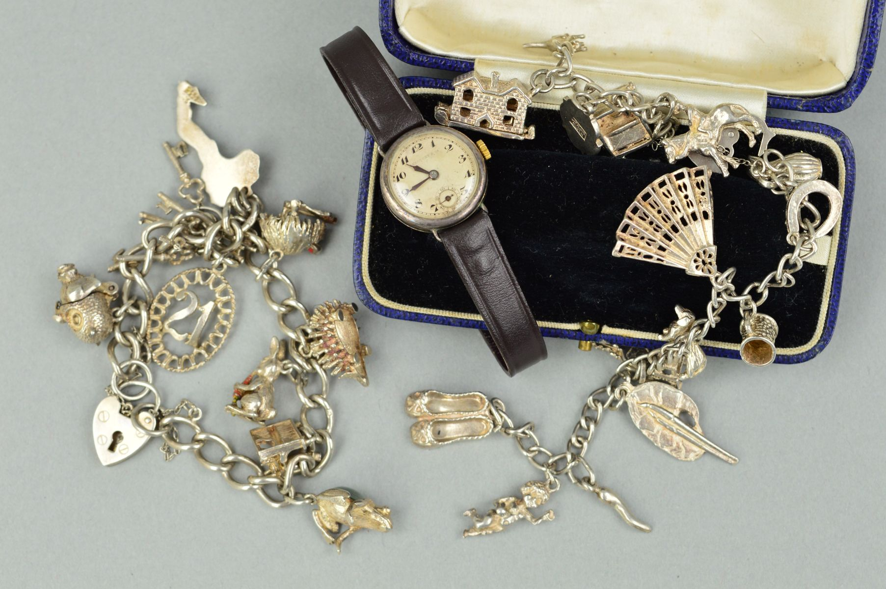Lot 22 - TWO CHARM BRACELETS AND A WATCH WITH ANTIQUE CASE, the charm bracelets on curb link chains