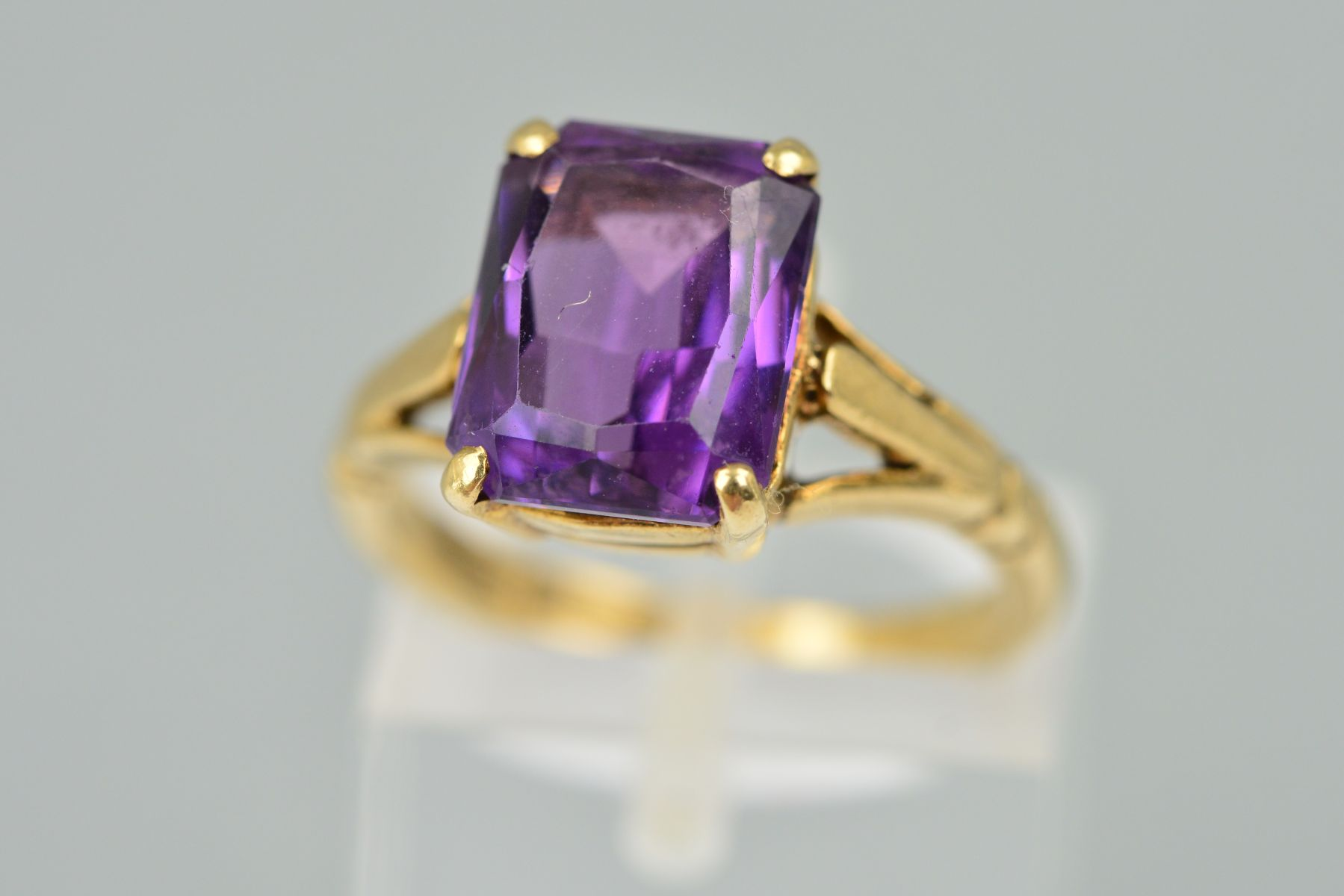 Lot 32 - A 9CT GOLD AMETHYST RING, the rectangular amethyst within a four claw setting to the branched