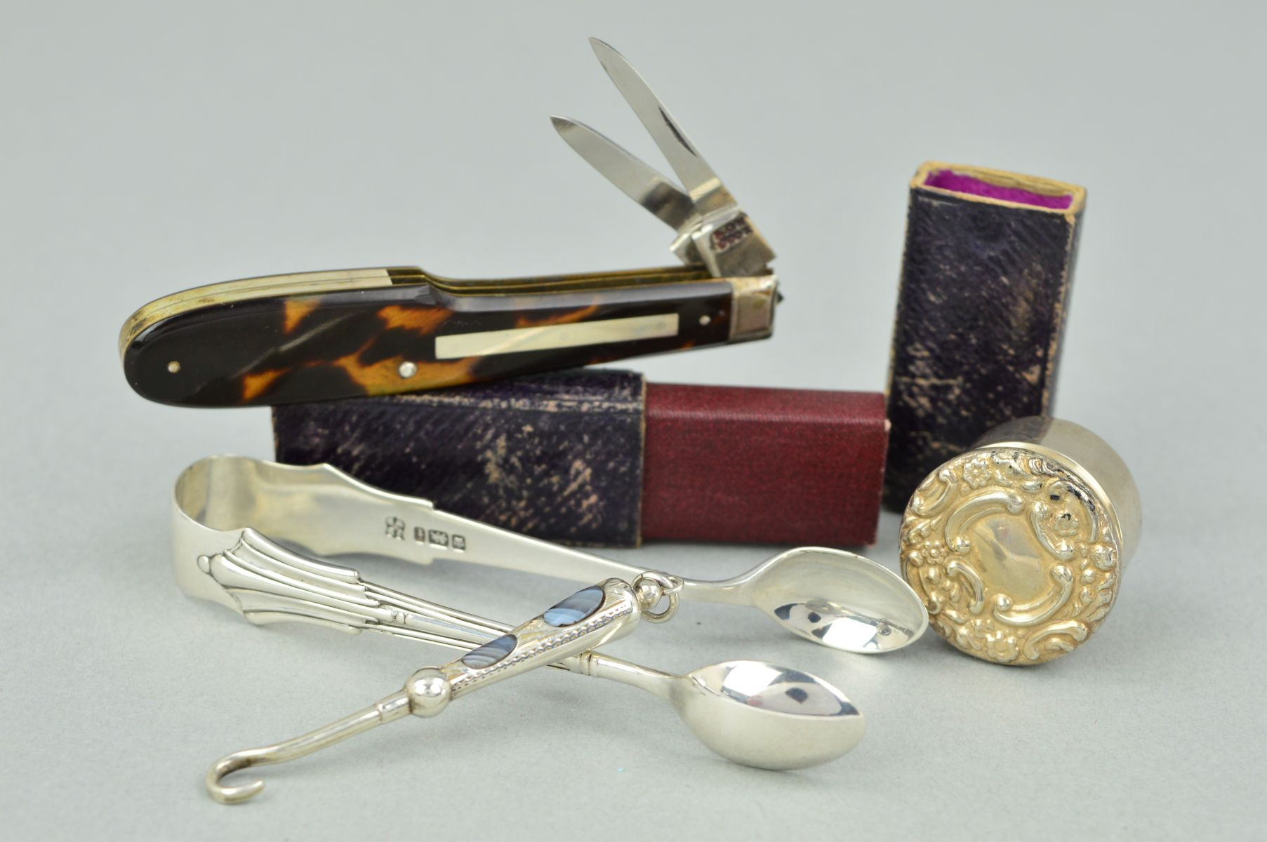 Lot 20 - FOUR ACCESSORIES to include a pair of silver sugar tongs, a silver circular pill box with embossed