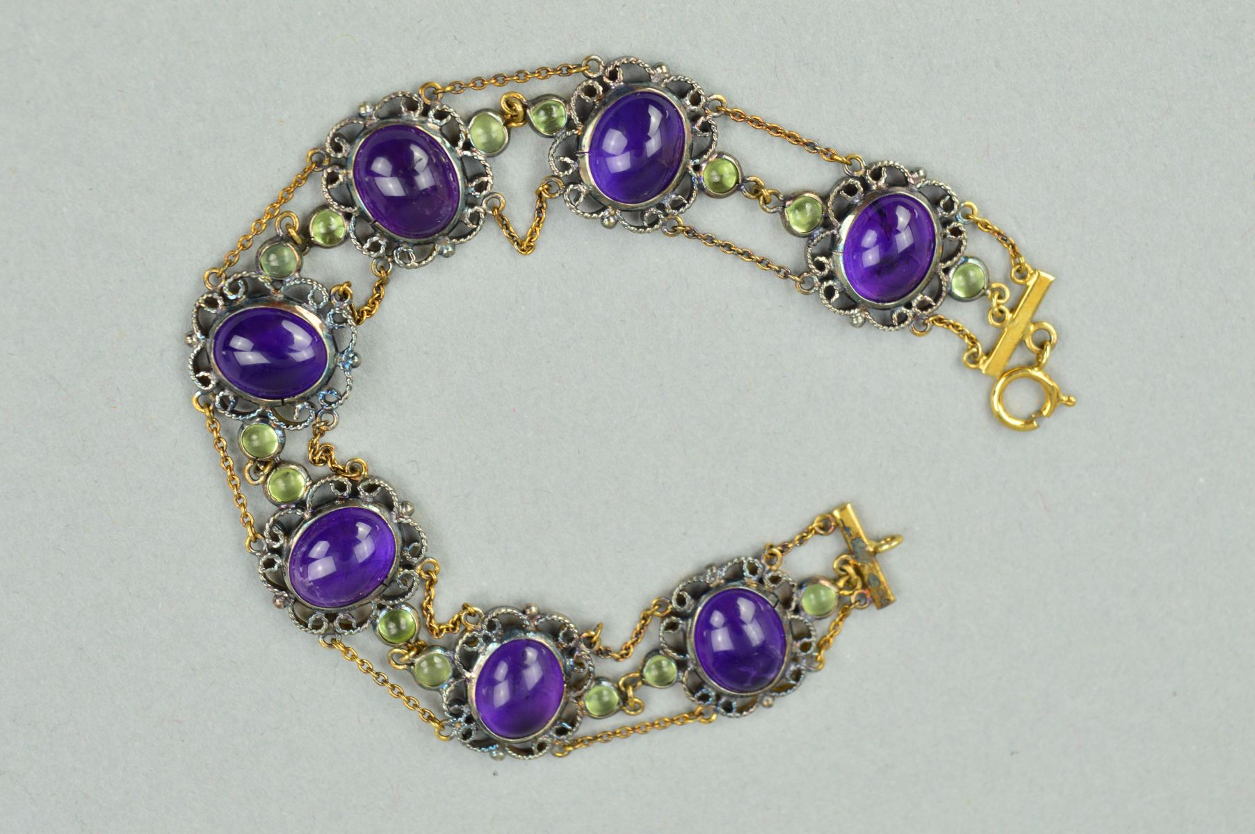 Lot 48 - A GEM BRACELET, designed as an oval amethyst cabochons within scrolling rope twist surrounds flanked