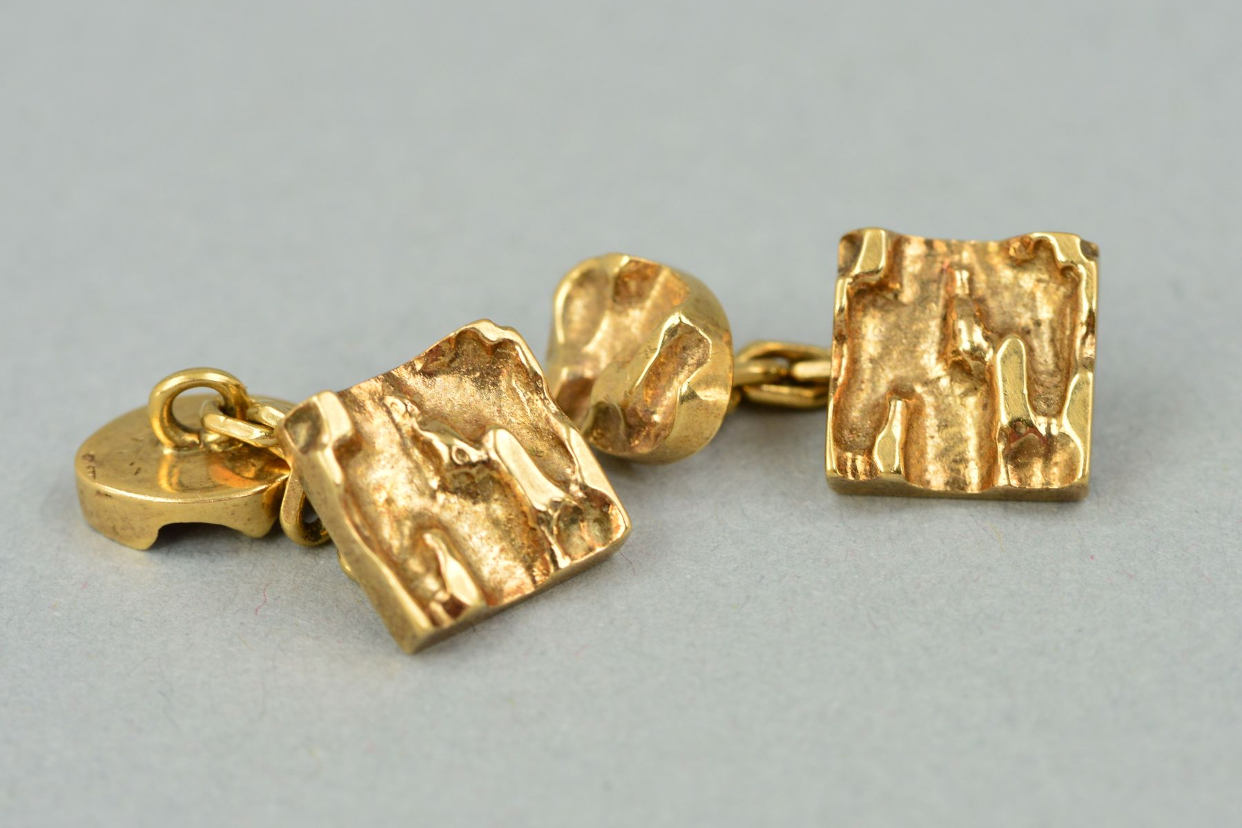 Lot 40 - A PAIR OF MID TO LATE 20TH CENTURY 9CT GOLD CUFFLINKS, abstract heavy carved design, chain