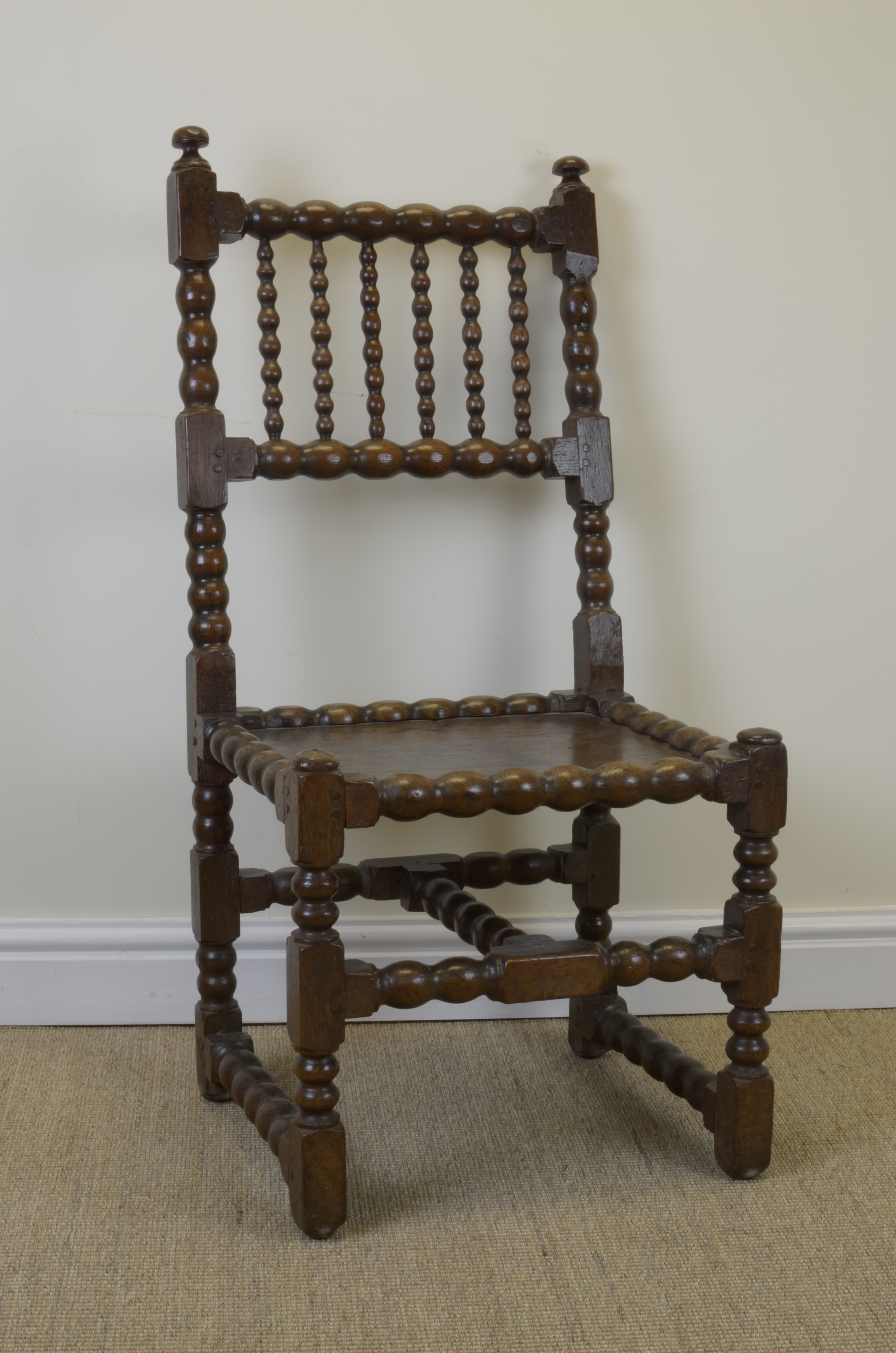 A 17th Century oak Side Chair with bobbin turned frame solid seat
