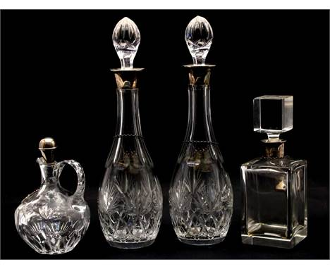 Four silver mounted glass decanters and stoppers, comprising: a cut glass pair, by Charles S Green & Co. Birmingham 1971,