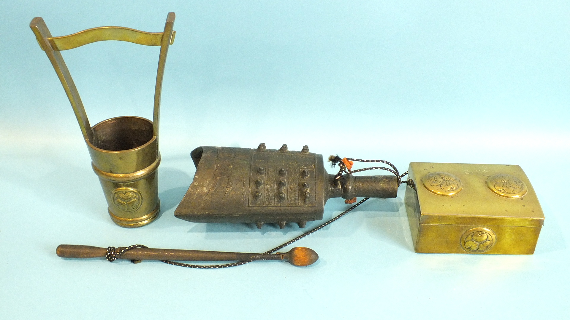 Lot 246 - A Chinese metal hand held gong of elliptical form, paper label within, wooden beater, (a/f) and