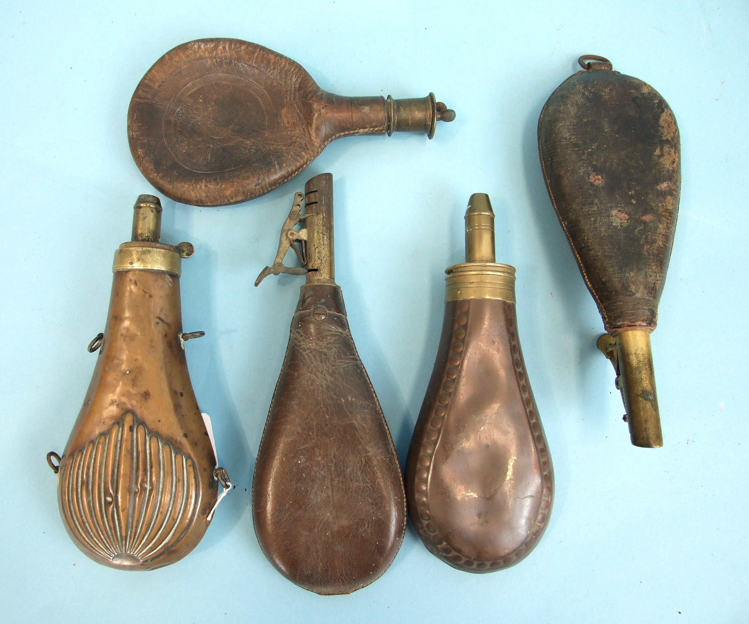 Lot 229 - Three 19th century leather shot and powder flasks and two brass powder flasks, (5).