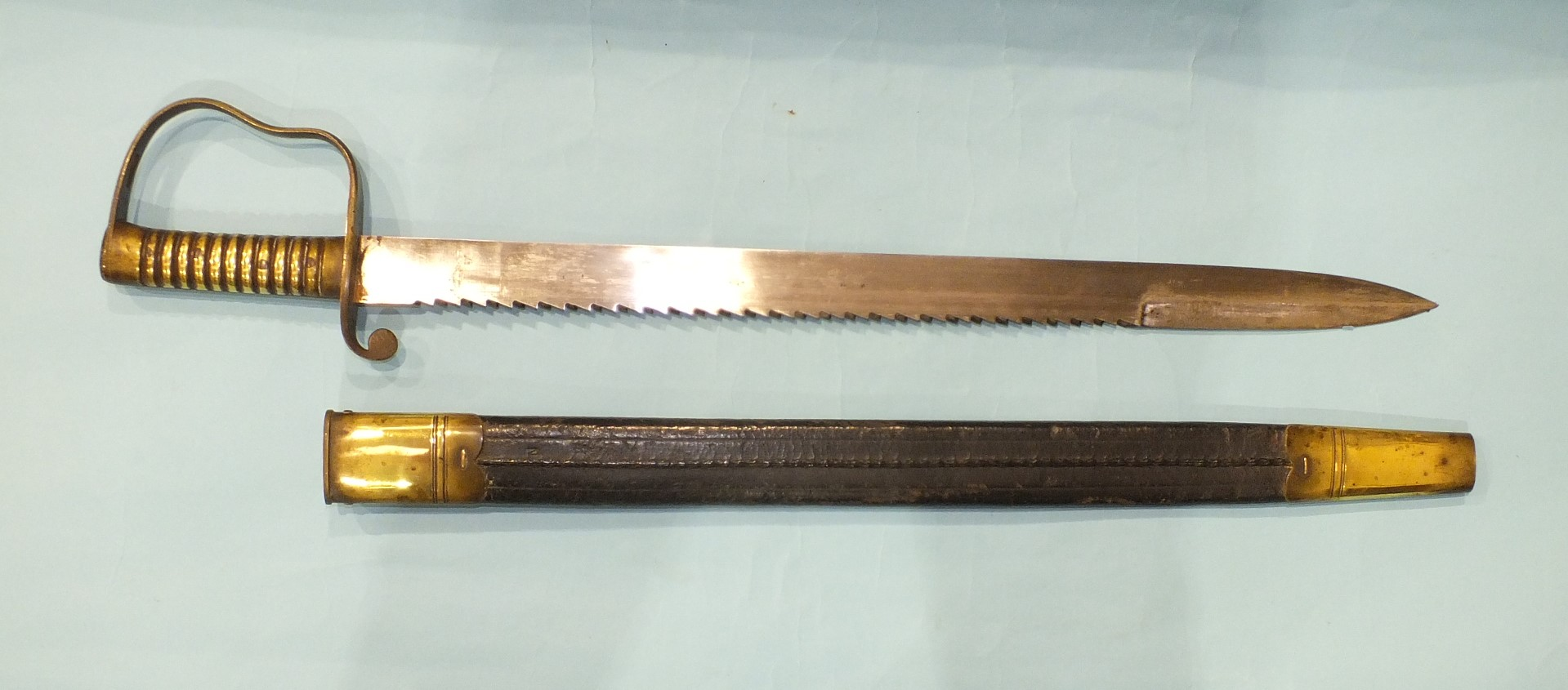 Lot 223 - A British Pioneer sword with brass hilt and saw backed blade, 57cm, marked with crown over B21 and