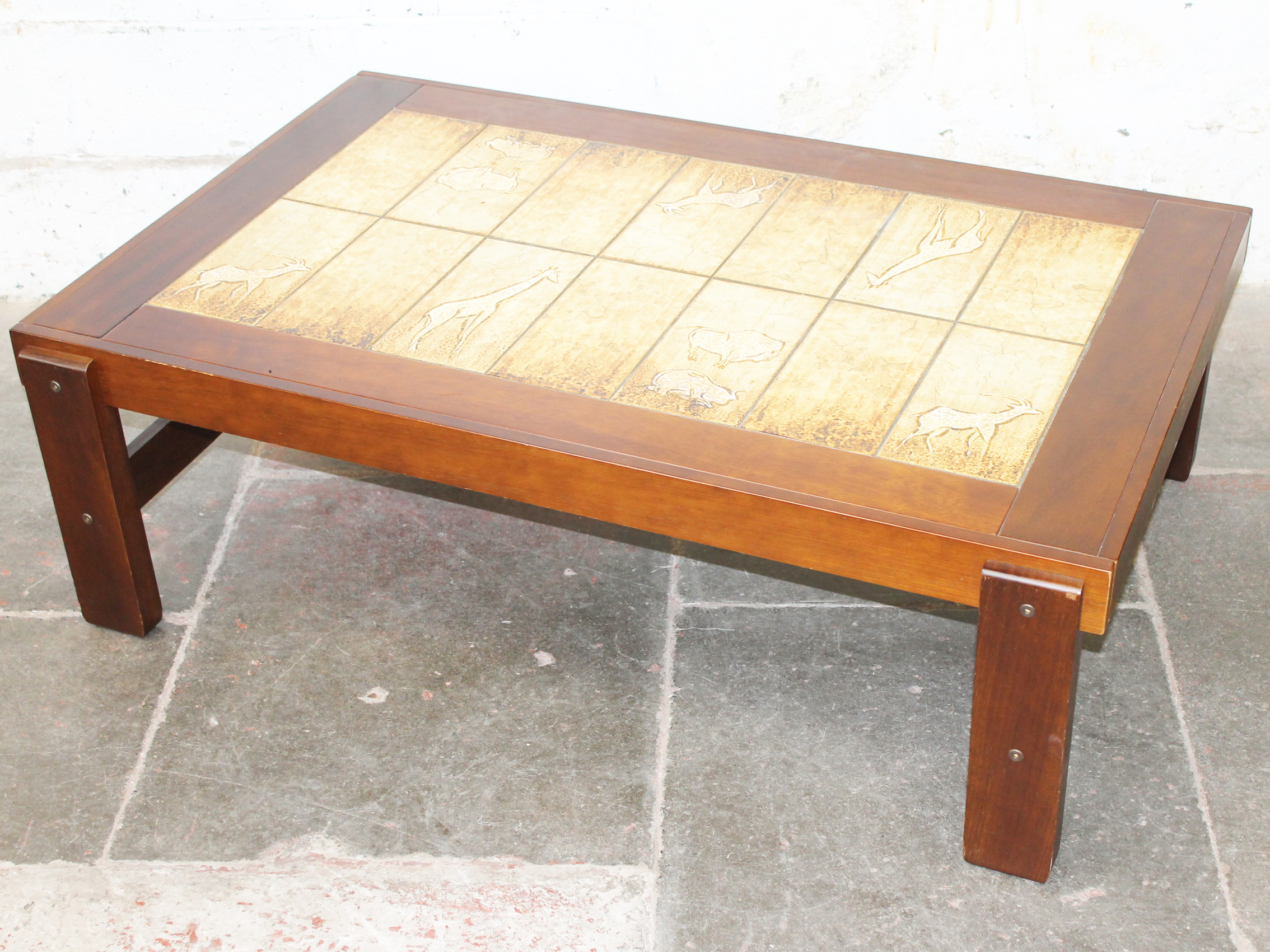 A 1970s coffee table having tiled top the tiles decorated with