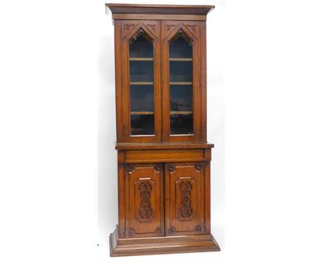A Victorian oak bookcase, in the Gothic style, the top with a shaped cornice above two arched glazed doors, each with pierced