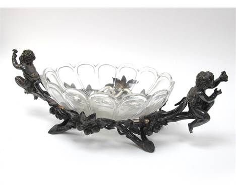 A Late XIX Century Christofle Table Centrepiece, the plated oval stand with two putti amongst flowering foliage, the heavy gl