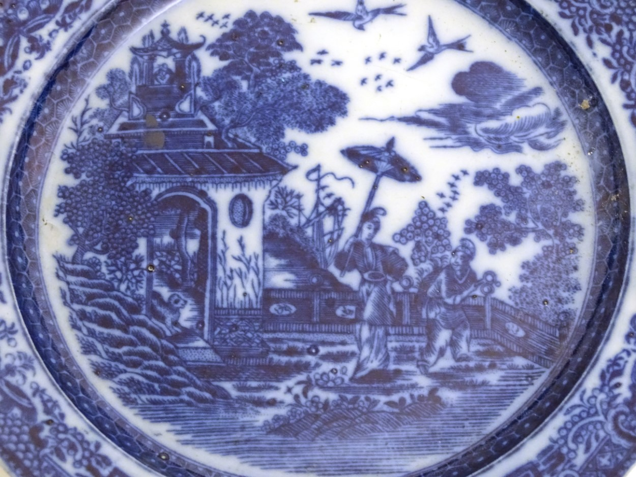 Lot 21 - A 19thC blue and white pearlware plate with a chinoiserie scene depicting a figure with a parasol