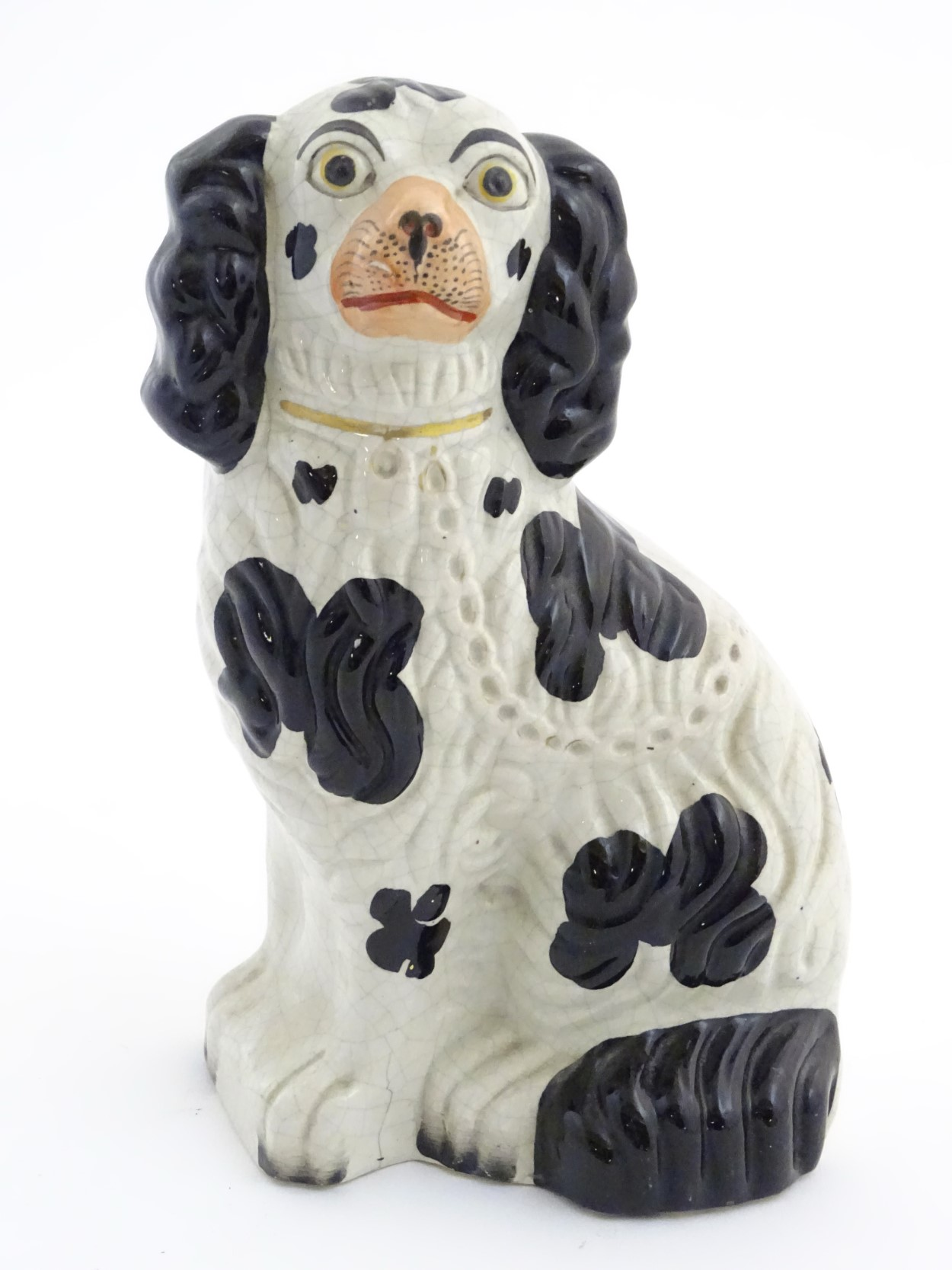 Lot 49 - A Victorian Staffordshire seated spaniel with black patch decoration and gilt lock and chain detail.
