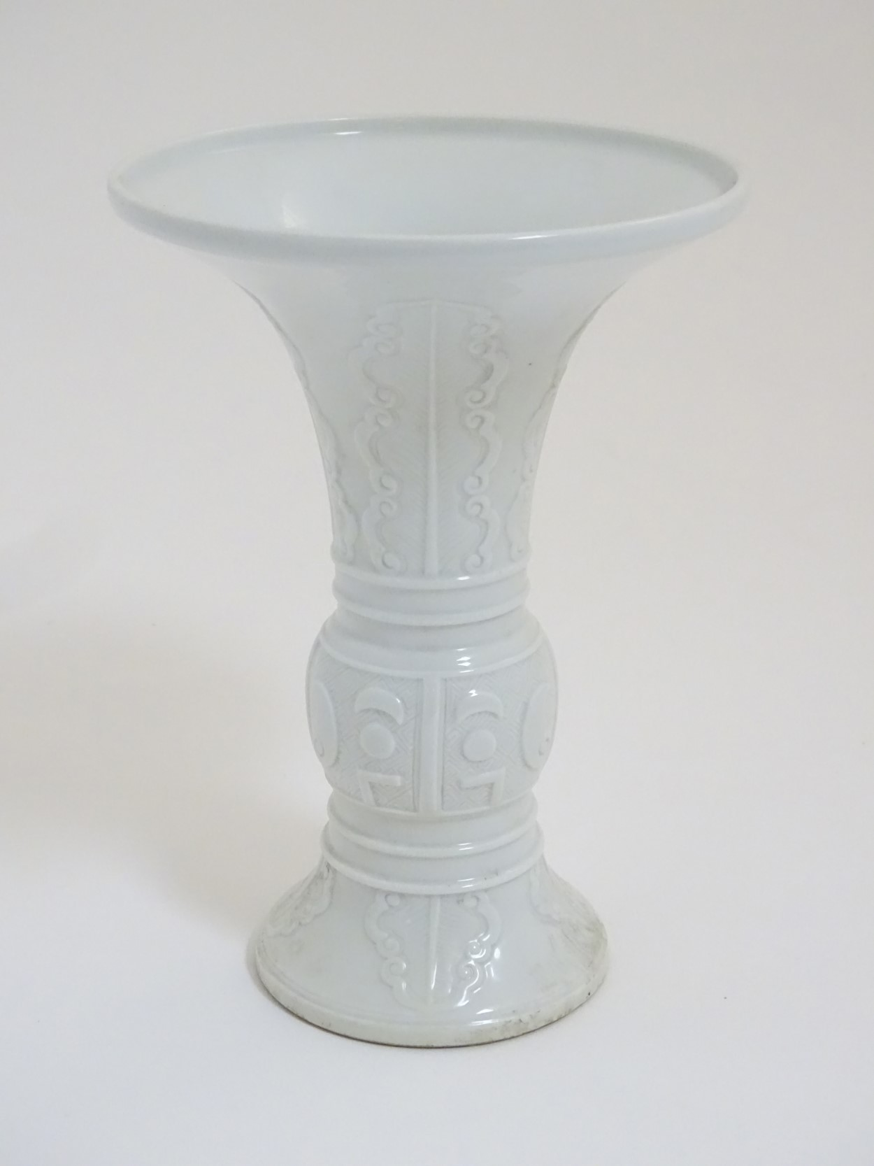 A Chinese white glazed Gu vase of archaic bronze design,