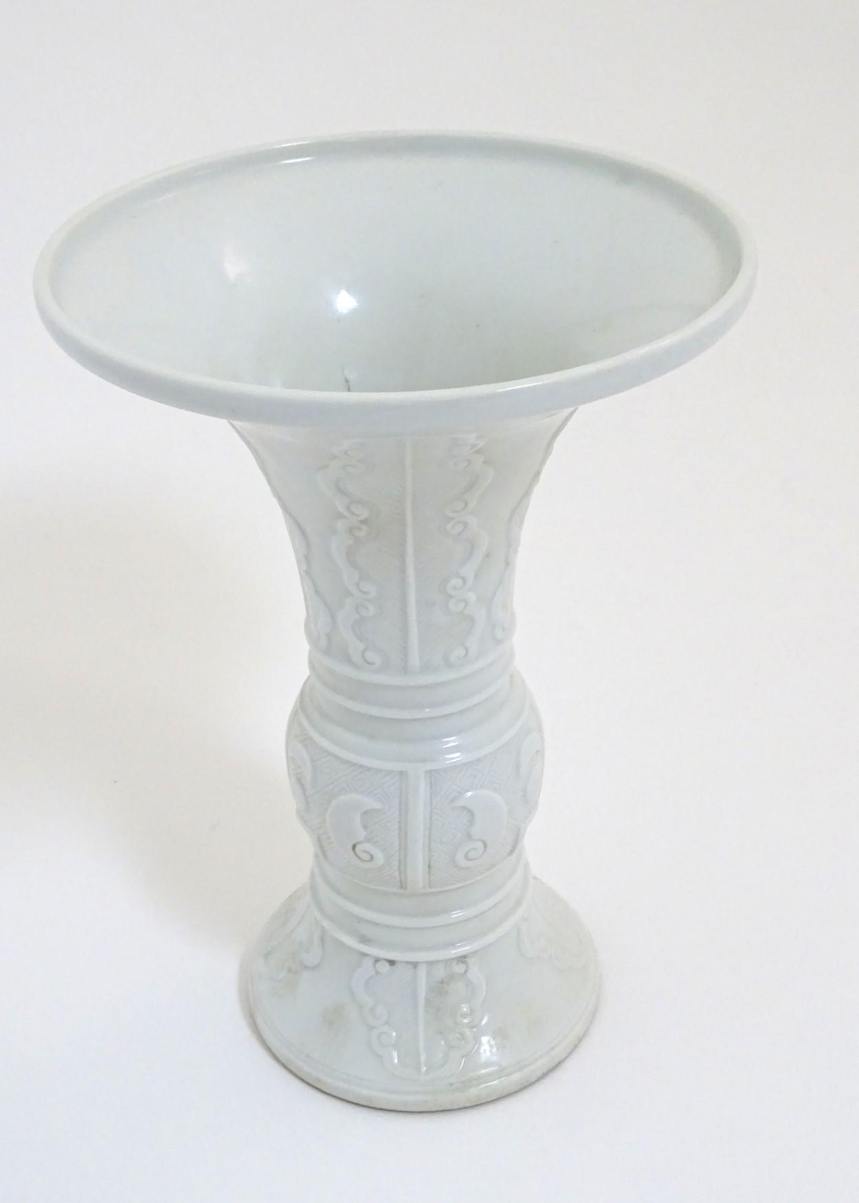 Lot 34 - A Chinese white glazed Gu vase of archaic bronze design,