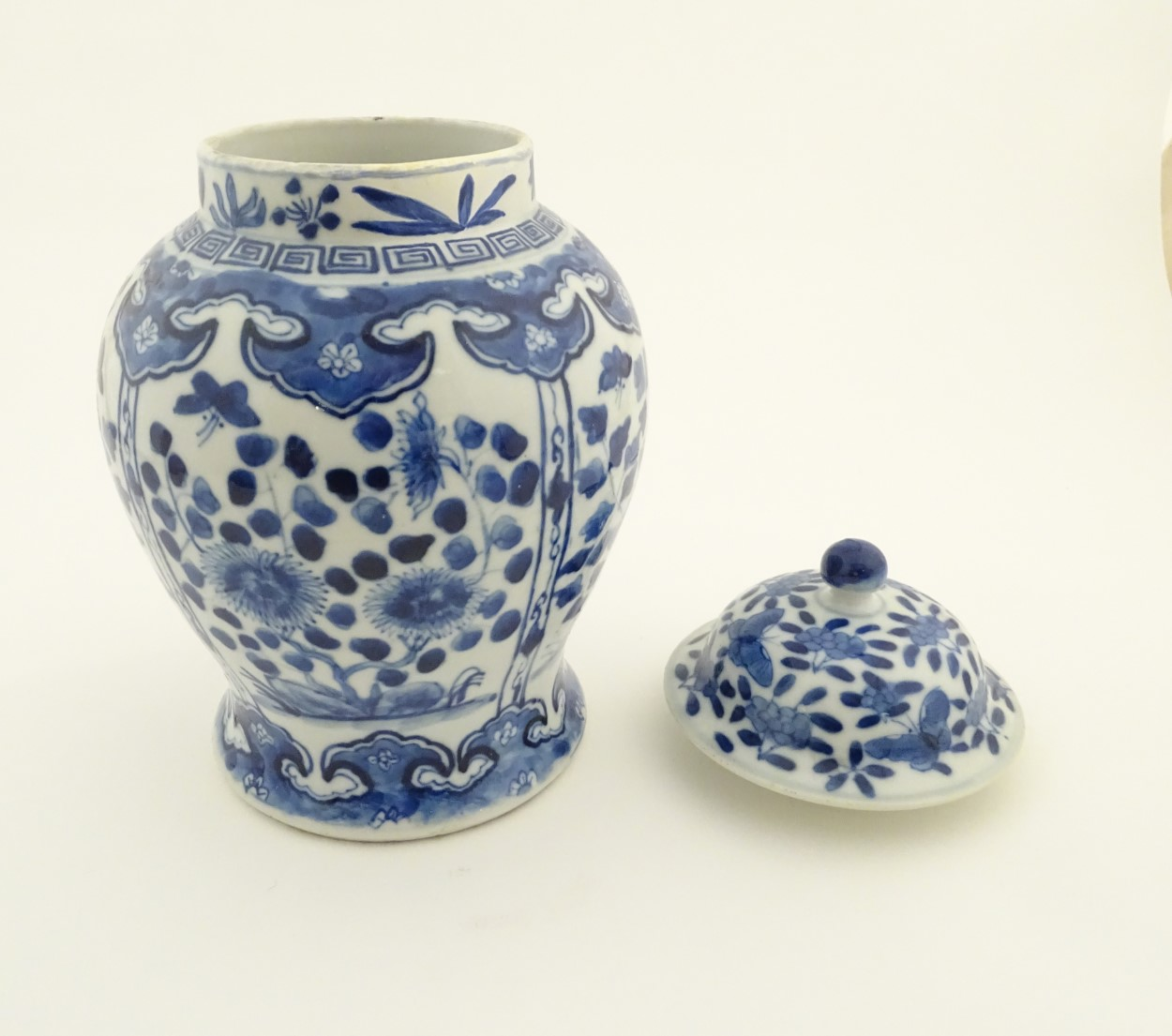 Lot 26 - A Chinese blue and white ginger jar with panelled floral and butterfly decoration,