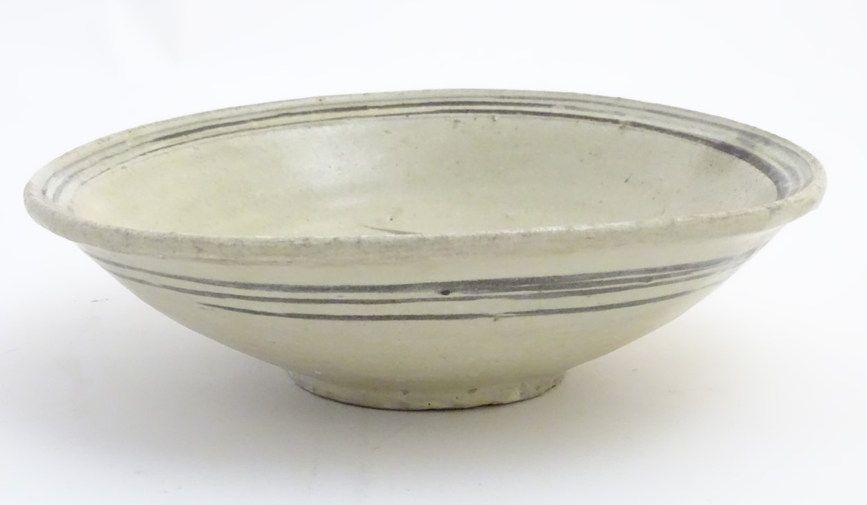 Lot 8 - A Chinese Ming Dynasty celadon glazed bowl with hand painted fish decoration to the centre and