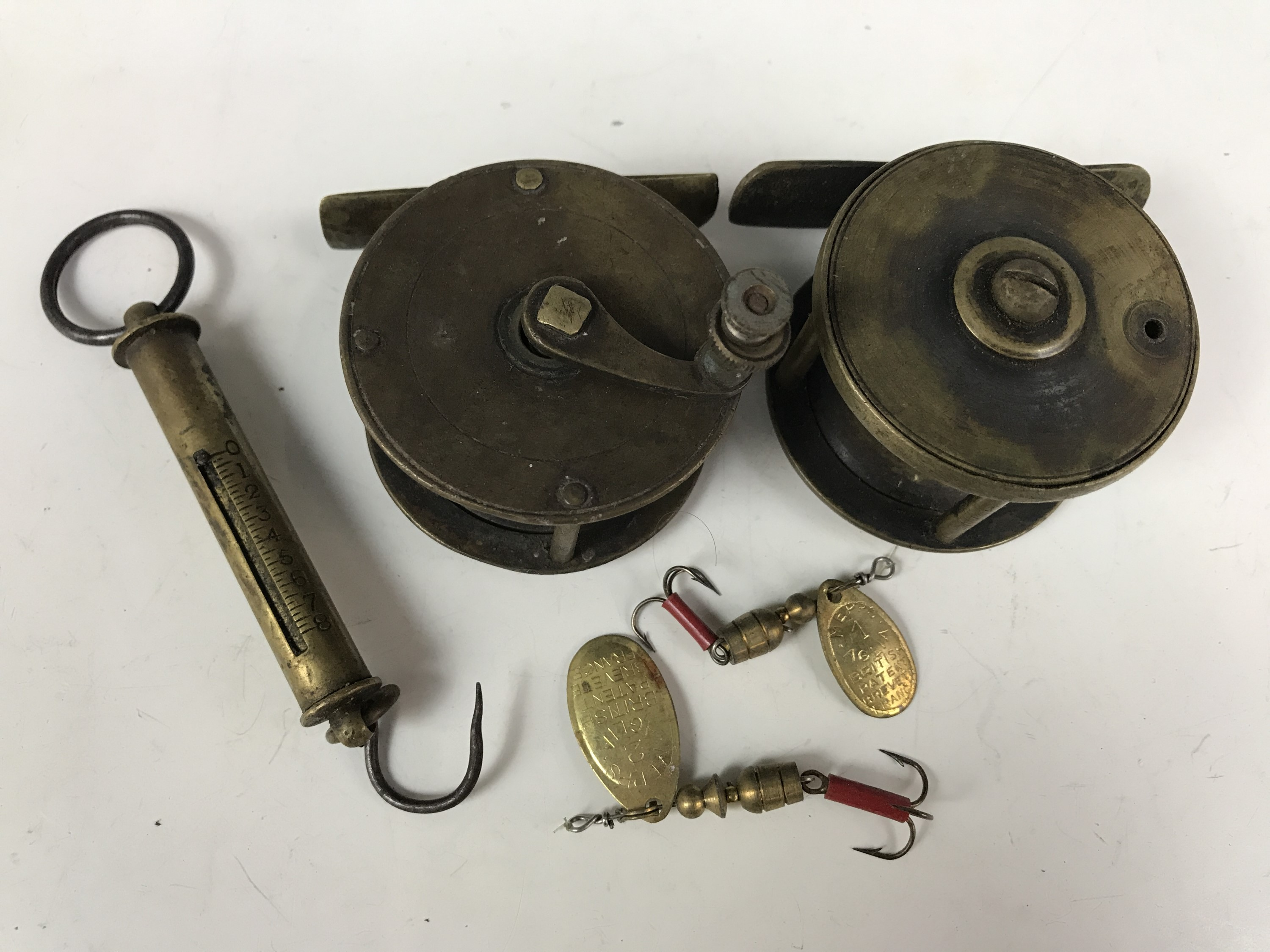 Lot 52 - Two vintage small brass fishing reels together with a brass spring balance and two Mepps spinners